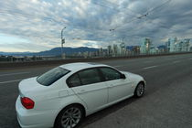 White car in front of the Skyline of Vancouver by stephiii
