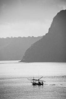 thai fisherboat in front of steep island by anando arnold