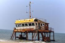 Ein rostiges buntes Schiffswrack ragt vor der Küste Sri Lankas in Asien aus dem Wasser von Gina Koch