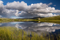 Huts on lake in landscape of Norway, Rondane NP by Bastian Linder