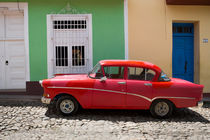 Red old car in front of colourful houses, Cuba by Bastian Linder