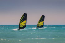 Two windsurfers ride parallel in sea by Bastian Linder