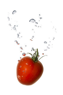 Cherry tomato in water with air bubbles by Bastian Linder