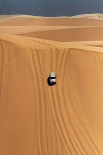 Four wheel drive descending a huge sand dune on a Sandwich H... by Danita Delimont