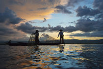 Intha fisherman rowing boat with leg at sunset on Inle Lake,... by Danita Delimont