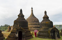 Monk holding red umbrella with Andaw-thein Temple, Mrauk-U, ... von Danita Delimont