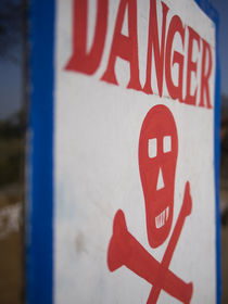 Skull and crossbones danger sign, Udaipur, Rajasthan, India. by Danita Delimont