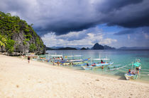 Outrigger boats before a storm anchoring on a sandy beach in... von Danita Delimont