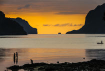 Silhouette of boys fishing at sunset in the bay of El Nido, ... von Danita Delimont