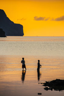 Silhouette of boys fishing at sunset in the bay of El Nido, ... by Danita Delimont