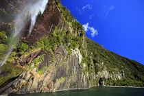 A tall waterfall drops off a steep cliff into the waters of ... von Danita Delimont