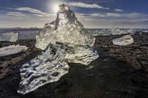 Scattered ice from icebergs on black sand beach at Joklusarl... by Danita Delimont