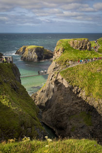 Tourists walk across the Carrick-a-Rede Rope Bridge along th... by Danita Delimont