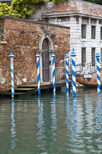 Gondola mooring posts in the canals of Venice by Danita Delimont