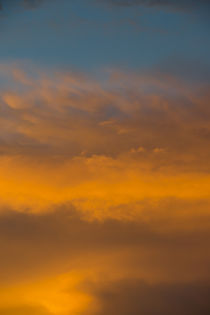 Clouds reflecting the orange sunset colors against the blue ... by Danita Delimont