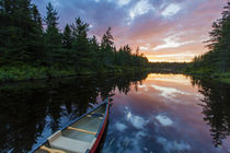 A canoe at sunrise on Little Berry Pond in Maine's Northern Forest by Danita Delimont