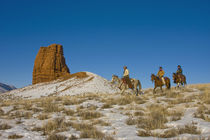 Cowboys on Ridge riding Horse through the Snow; Model Released by Danita Delimont
