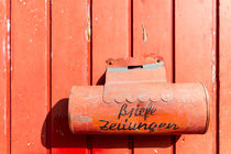 Red mailbox on a red wall by domi