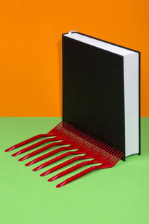 Still life with a black book and red forks on a colored background by Valentin Ivantsov