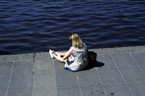 Eine Frau sitzt in sich versunken am Wasser. von fischbeck