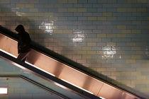 Mann mit Kapuze auf Rolltreppe  by Bastian  Kienitz