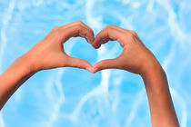 Two little hands forming heart over swimming pool von Silvia Eder