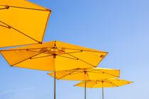 Gelbe Sonnenschirme vor blauem Himmel von Christoph Hermann