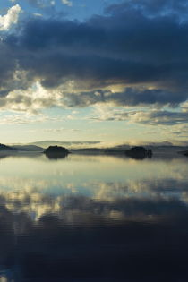 Two islands and the cloudy sky are reflected in a glassy lake von Intensivelight Panorama-Edition