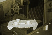 Flower patterned tea cups are laid out on a doily near the helm of a vintage wooden boat - sepia von Intensivelight Panorama-Edition