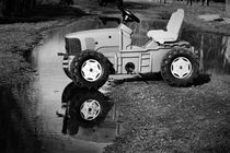 Abandoned toy tractor in a puddle von Maud de Vries