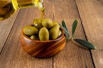 Olivenöl und grüne Oliven in Holzschale - Olive oil and green olives in wooden bowl von Thomas Klee