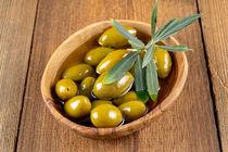 Grüne Oliven mit Zweig in einer Holzschale - Green olives with twig in a wooden bowl von Thomas Klee