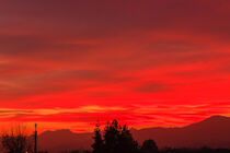 a spectacular sunset over the mountains paints the sky of pink by susanna mattioda