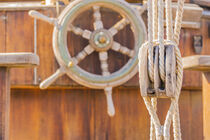 Old sailing boat deck with nautical pulley and vintage wooden helm wheel by Alex Winter
