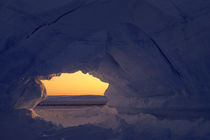 ICEBERG WITH ARCH AND EMPEROR PENGUIN COLONY IN BACKGROUND von Wolfgang Kaehler