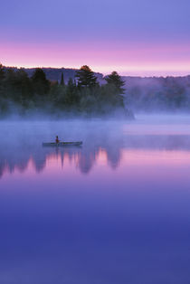 Canada, Ontario, Algonguin Park, Canoeist on lake at sunrise.   Credit as von Danita Delimont