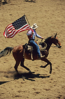 USA flag at rodeo opening ceremony (NO MODEL RELEASE) by Danita Delimont