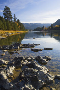 Clouds and distant mountains reflected in rocky Kootenai River, Montana, USA. by Panoramic Images