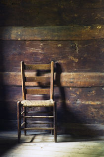 Ladderback chair in empty room by Panoramic Images