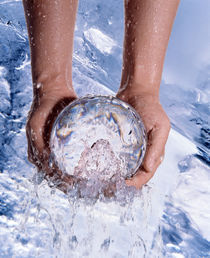 Close up of a pair of hands pulling crystal ball from rushing water by Panoramic Images