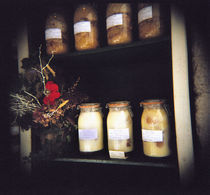 Jars and flowers in racks by Panoramic Images