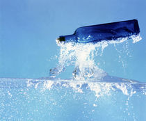 Blue glass bottle falling through water with splash von Panoramic Images