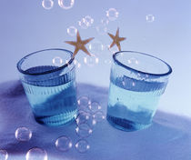 Two glasses under water with bubbles and two gold stars by Panoramic Images