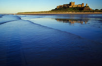 Gentle waves on Northumbrian coast, distant Bamburgh Castle, Bamburgh, England. von Panoramic Images