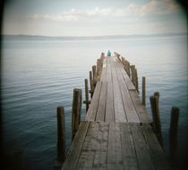 Person sitting on a pier, Lake Bolsena, Italy by Panoramic Images