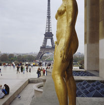 'Gilded statue of a woman with a tower in the background' by Panoramic Images