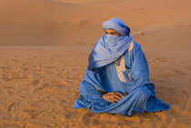 Veiled Tuareg man sitting cross-legged on the sand, Erg Chebbi, Morocco von Panoramic Images