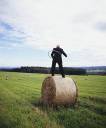 Rear view of a man standing on a hay bale playing with a plastic hoop, Germany by Panoramic Images