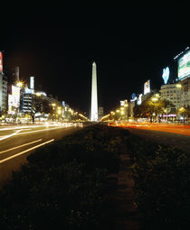 Obelisk lit up at night in a city by Panoramic Images