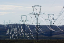 High voltage power lines spanning rolling hills. by Panoramic Images